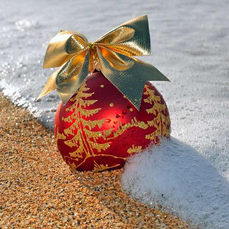 Christmas decoration on the beach against ocean wave photo