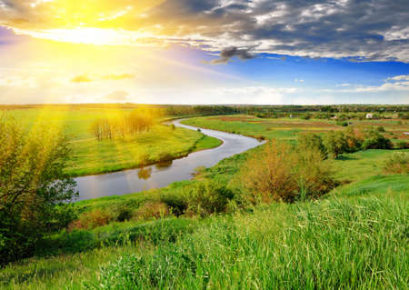 Spring meadow, meandering river, bright sun and blue sky in the evening. Stock Photo