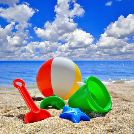 Baby Toys on beach sand against the blue sky