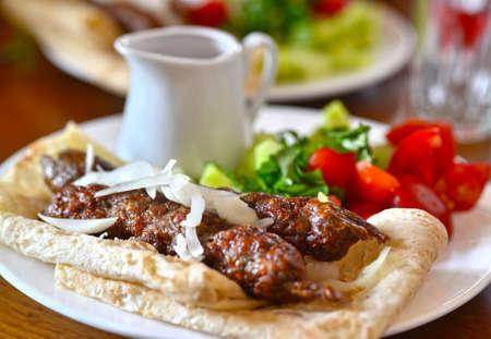 pita bread: Skewers of lamb. Kebab in pita bread with sauce and vegetables. Georgian cuisine. Georgia. Tbilisi.