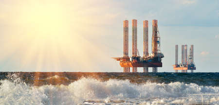 Sea station of gas production. Drilling platforms in the sea at sunrise against a blue sky