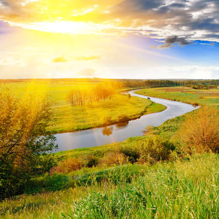 The bright evening sun over the river and green meadows