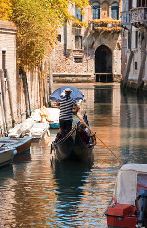Gondola sails in a canal among ancient houses in autumn sunny day in Venice, Italy. Boats moored to the walls of houses