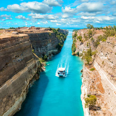 Beautiful scenery of the Corinth Canal in a bright sunny day against a blue sky with white clouds. Among the rocks floating white ship in turquoise water. Stock Photo