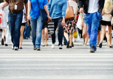 caminando: Motion borrosa peatones que cruzan la calle iluminada por el sol
