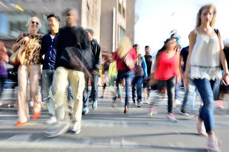 Zoomen en motion wazig menigte het oversteken van de straat. Blur-effecten die in de lens, niet verwerken posten. Stockfoto