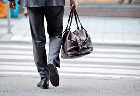 Man in suit with bag, on zebra crossing Standard-Bild