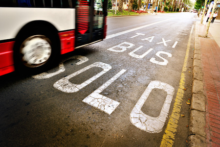 express lane: Bus in bus lane out of focus, traffic. Bus and taxi sign painted on street in focus. Stock Photo