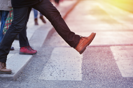 Man taking the step (onto zebra crossing) Standard-Bild