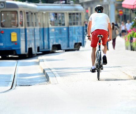Bike commuter and tram in sunlit city Standard-Bild