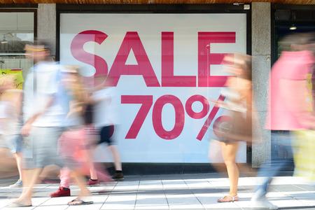 Shop sale sign, motion blurred pedestrians