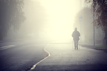 autumn path: Woman walking in the fog