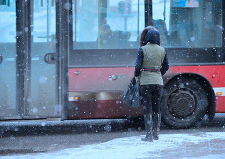 Femme d'attente pour le bus dans la tempête de neige