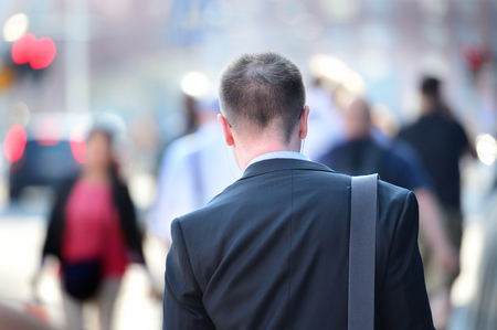 Suit in silhouette, sidewalk crowd Stock Photo