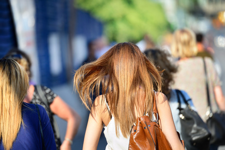 Woman with bag walking in crowd on sidewalk