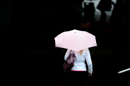 Woman with umbrella against black