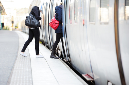 Women in hurry enters train Stock Photo