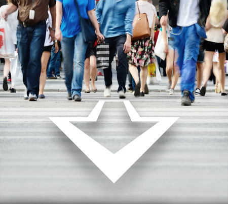 Motion blurred pedestrians crossing street, arrow