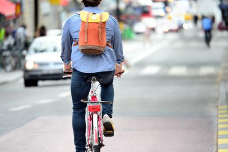 Commuter on bike in traffic Stock Photo