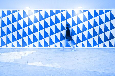 Motion blurred pedestrian against patterned wall