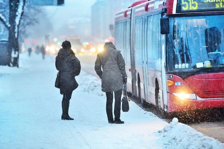 吹雪の中到着したバスを待っている通勤者