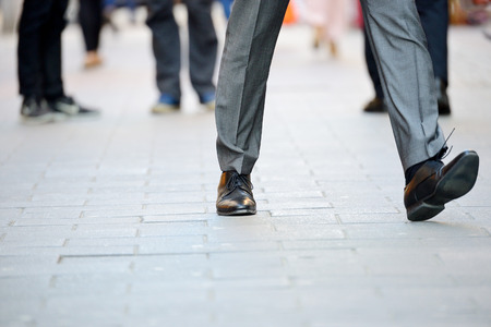 moving forward: Business man in suit taking a big fast step forward