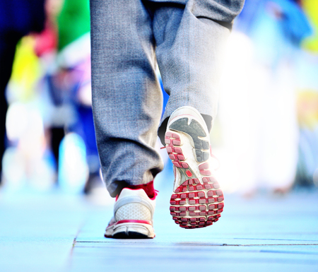 Close up of shoes walking on street into bright light
