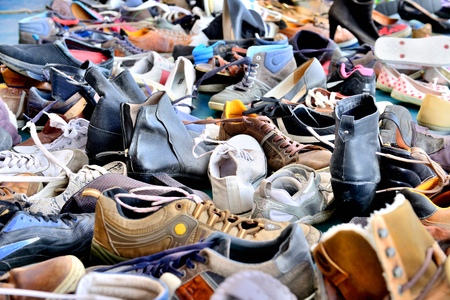 Shoes, lots of used in pile Standard-Bild