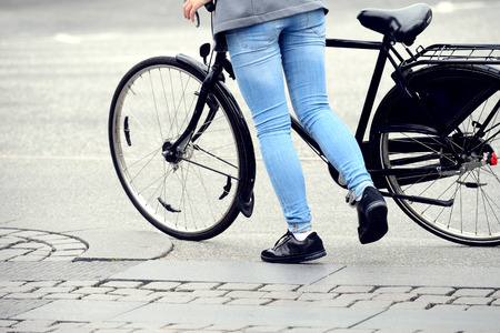 Person getting on bike Stock Photo