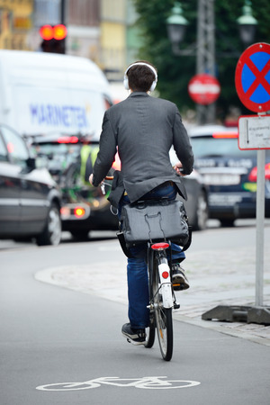 Male bicyclist on the street, with headphones