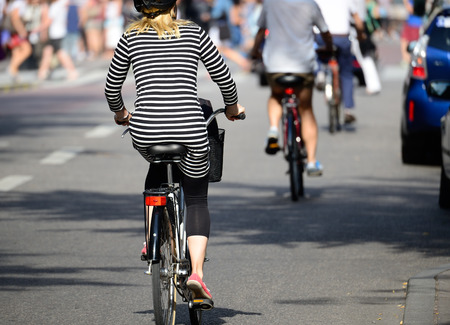 Blonde woman with helmet on bike in traffic