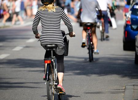 Blonde woman with helmet on bike in traffic