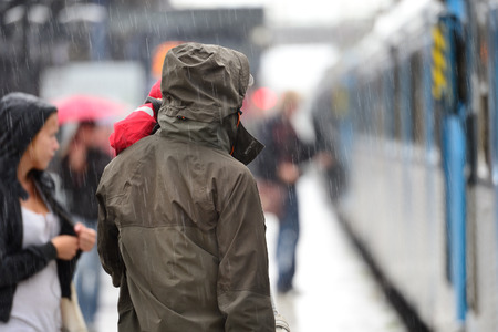 Man in raincoat in heavy rain on train station platform Stock Photo