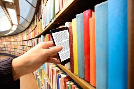 La cueillette à la main un ordinateur tablette sur étagère dans la bibliothèque Banque d'images