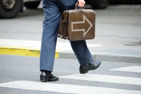 Bag with arrow. Suit (man) in silhouette walking on the street with bag.