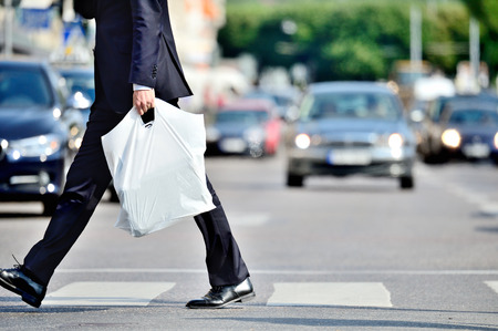 Man in suit with plastic bag crossing street Foto de archivo