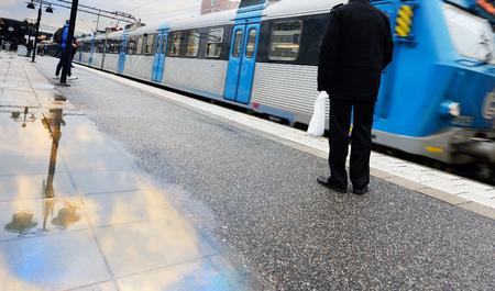 Les voyageurs en attente pour le train d'arrêter sous la pluie