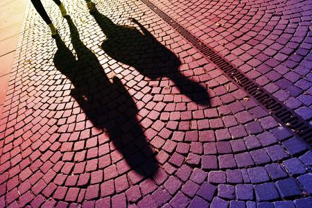 Les gens marchant ombres sur les pavés