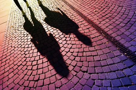 People walking casting shadows on cobblestones Stock Photo