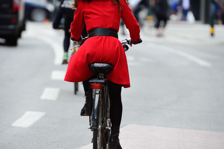 Woman in red on bike. Bike lane symbols on ground.