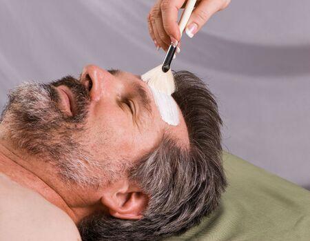 resurfacing: Older man getting full facial at spa