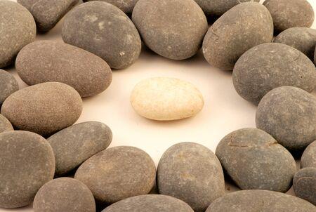 white pebble: Closup of white stone surrounded by grey stones Stock Photo