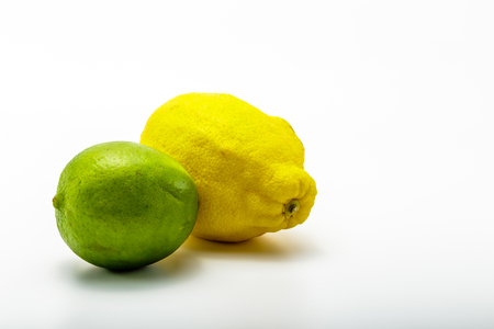 florida citrus: A pair of lemon and lime fruits isolated on a white background.  The lemon is yellow and the lime is green.   The fruits are whole Stock Photo
