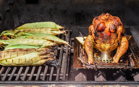 A fully roasted beer can chicken on a grill with a half dozen grilled corn on the cob. Stock Photo