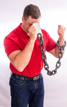 Adult man in distress, shackled to his cell phone.  Man showing facial expressions of agony and hopelessness Stock Photo