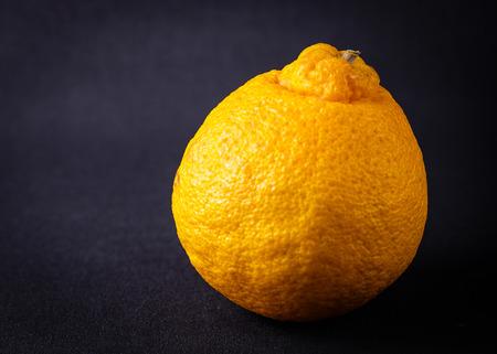 A whole mandarin orange on a black background Stock fotó