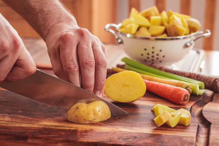 Chopping potatoes for homemade chicken and white bean soup.  Ingredients include potatoes, carrots, and celery.