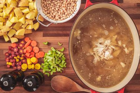 Overhead view of the ingredients used to make homemade chicken and white bean soup.  Ingredients include sliced carrots, celery, potatoes, and white beans.  Homemade chicken soup stock is in the pot. Stock Photo
