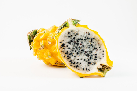 Two yellow dragon fruits on a white background.  One of the fruits is sliced in half.