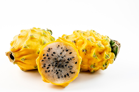 Three yellow dragon fruits placed in a pile isolated on a white background.  one of the fruits is sliced in half. Reklamní fotografie